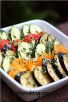 Кружочки овощей уложить внахлест слоями в жароупорной посуде, обильно посолить, поперчить и равномерно смазать ароматным маслом с чесноком и травами.