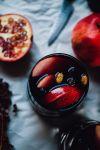 В большом кувшине объединить красное вино, коньяк, гранатовый сок, гранатовые зерна и яблочные дольки. Выжмите половину лимона в смесь. Затем тонко нарежьте другую половину лимона и добавить дольки в кувшин. Добавить измельченные стручки кардамона и корицы. Перемешайте.